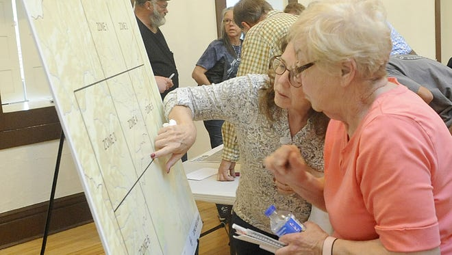 Kathie Senseman (right) and other Dayton residents look at where their properties lie on a flood zone map.