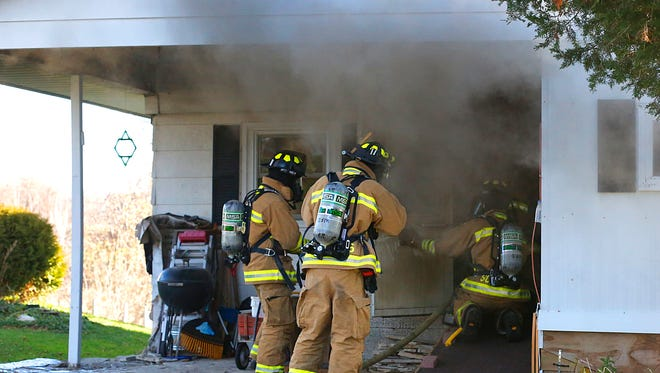 Waupun firefighters enter a home on fire at N3419 Center Road on Thursday.