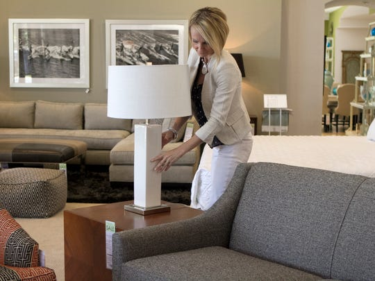 Melanie Burton, of Robb & Stucky International, replaces a lamp on a side table while helping clients.