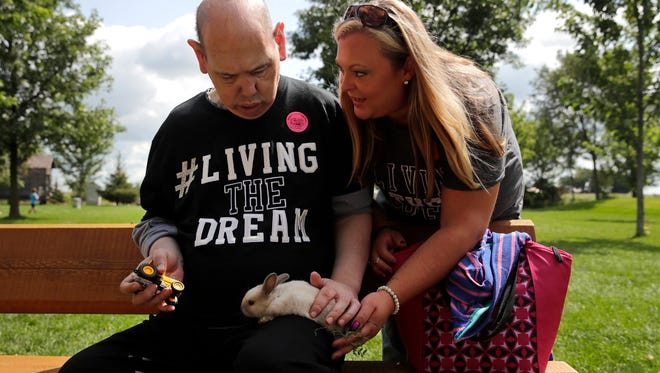 Phillip Fischer, a participant in Agape of Appleton's Project Live Your Dream, is handed a rabbit by Emily Luebke, an Agape staff member, at Mulberry Lane Farm in Hilbert.