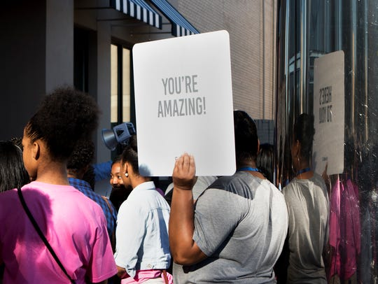 "Toni Jenkins holds a sign reading ""You're Amazing"""