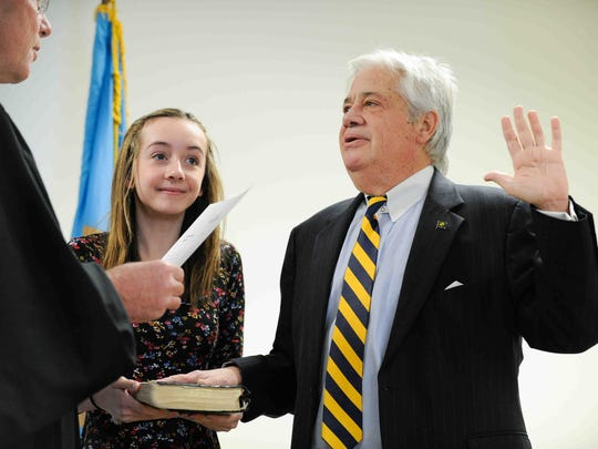 Delaware Supreme Court Justice Henry duPont Ridgely (left) swears in R. Thomas Wagner Jr. as state auditor as Maddie Bergold, 11, daughter of R. Thomas Wagner, Jr. holds the Bible.