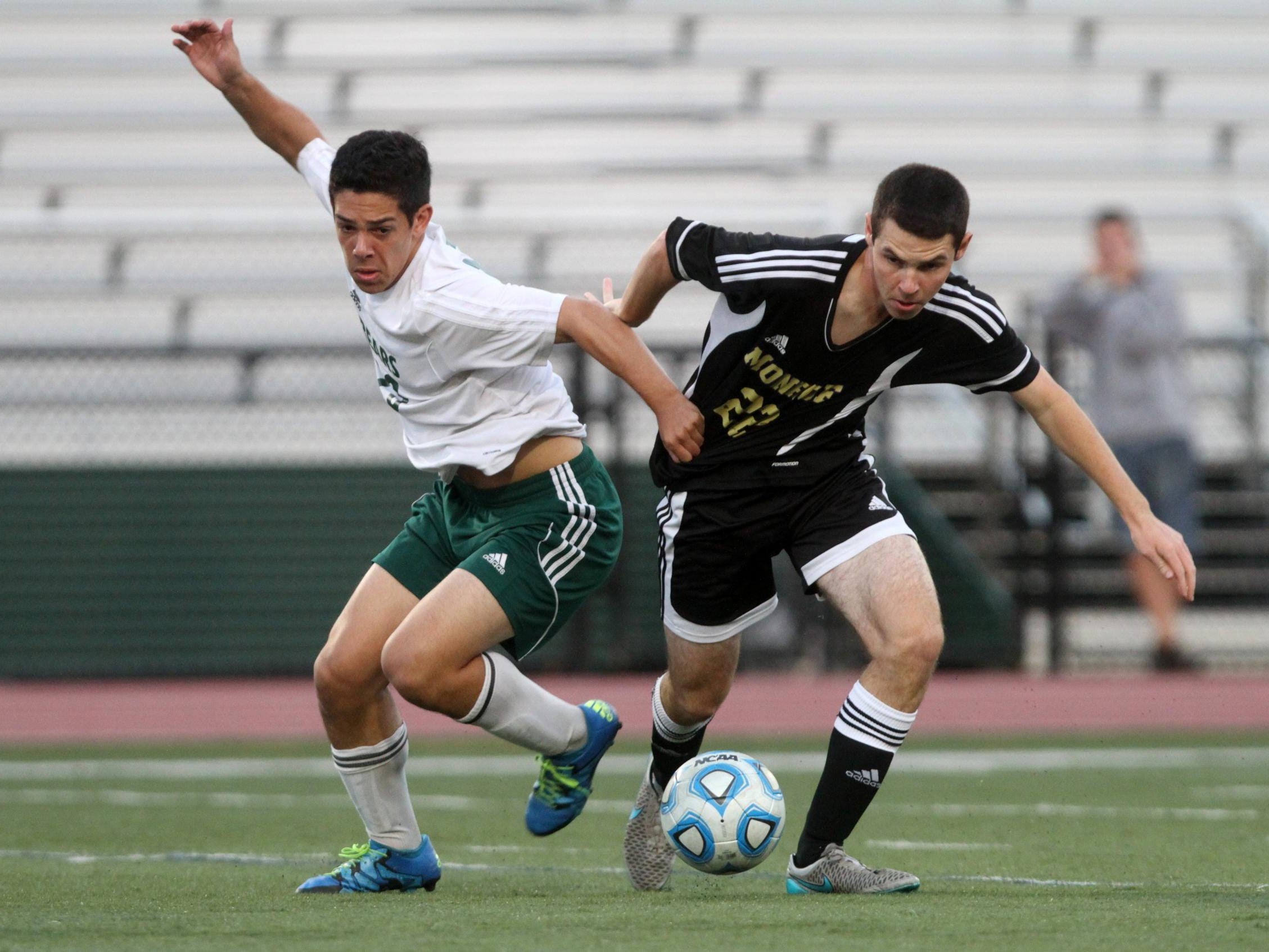 East Brunswick's Jason Kramer battles with Monroe's Ryan McCabe during the first half on Thursday in East Brunswick.