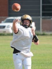Abilene High quarterback Andrew Ezzell throws a pass during practice Tuesday at the Eagles' on-campus practice field.