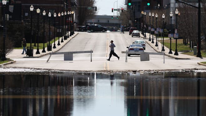 A jogger passed flood waters at the intersection of Preston and E. Witherspoon in Louisville, Kentucky