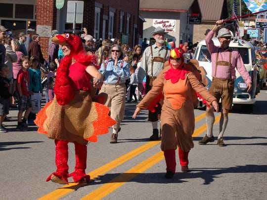 Two turkey-costumed parade participants skip and dance down the parade route during the 2016 Turkey Trot parade sponsored by the Mid-Marion County Rotary Club. The club has announced it will be the new sponsor for the festival moving forward.