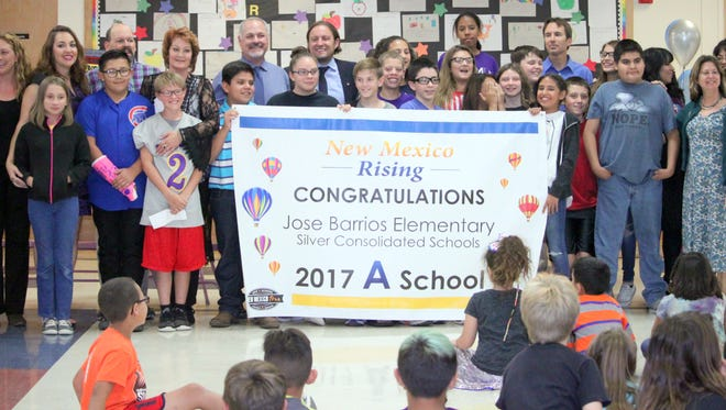 Sixth grade students and teachers along with staff at Jose Barrios Elementary School show off a banner presented to them by the New Mexico Public Education Department for getting a school grade of an A this year.