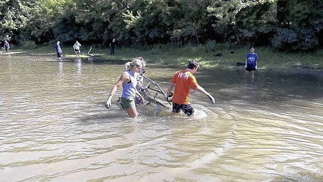 Volunteers pull a shopping cart from the Olentangy River during the city's 2019 river cleanup at Mingo Park. 500 E. Lincoln Ave. This year's event is still on, albeit with a much smaller crowd and health-related protocols.