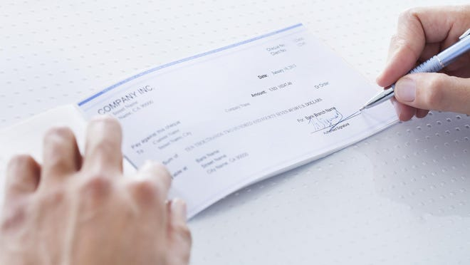 Close-up of hand filling out a check.