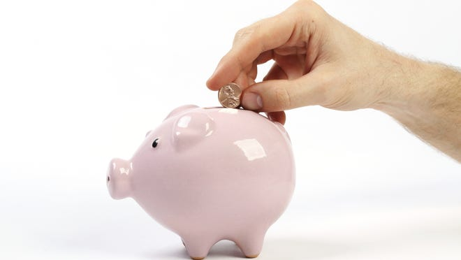 Piggy bank style money box with penny falling into slot
