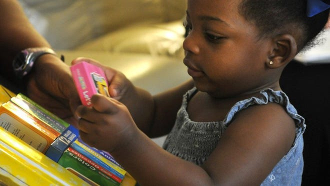 TORIN HALSEY/TIMES RECORD NEWS Makyha Johnson, 1, picks out a book at her home. The child and her mother, B.J. Redmon, receive regular visits from a nurse in the Nurse-Family Partnership program administered through the United Way and funded by state grant money.