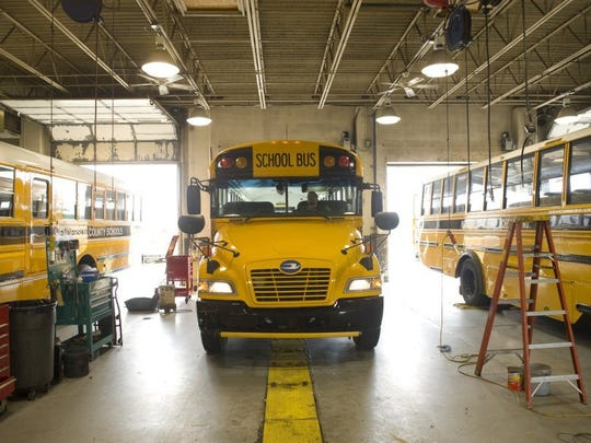 A steady stream of school buses enter and exit the Henderson County Schools Transportation Department garage for maintenance before the new school year.