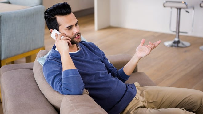 Man calling on the couch in the living room