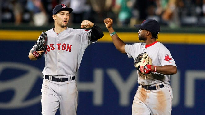Red Sox left fielder Grady Sizemore and center fielder Jackie Bradley Jr. celebrate a victory against the Braves in the ninth inning at Turner Field.