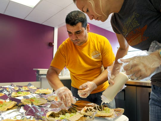 Yassin Terou prepares falafels and hummus with assistant Tiffany Teague in 2014.