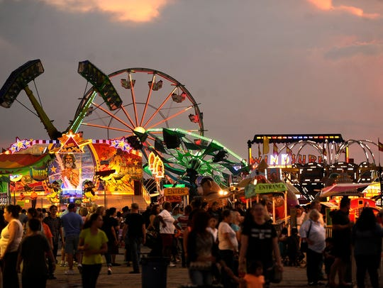 The sun sets as fair patrons walk the midway during
