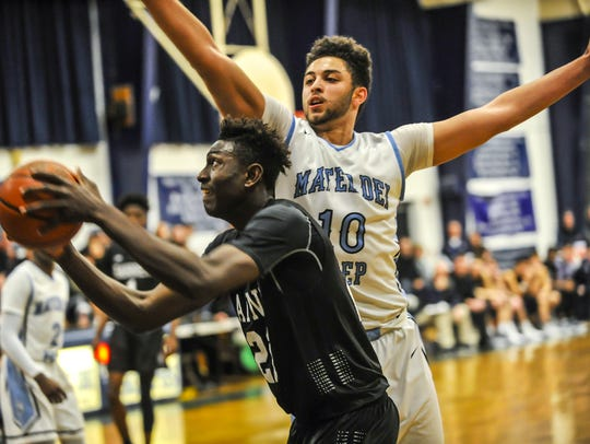 Savior Akuwovo of the Ranney School, left, looks for a shot despite tight pressure by Adam Afifi of Mater Dei Prep in a game on Feb. 5 in Middletown.