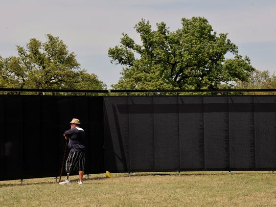 Michael Hogan contemplates The Wall That Heals Thursday. Hogan said he wasn't a veteran and didn't think he knew anyone on the wall, but still felt it was important to come see it.
