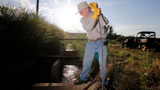 Mike Carruthers, clears debris on Aug. 15 before opening the Stacey Ditch at Sutherland Farms in Aztec, N.M.