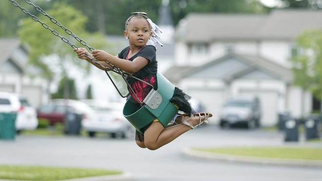 Tahani Smith, 4, rides a swing at the playground of Crerand Commons in Gates, where she lives with her mother, Tyesha Boone, and her sisters, Trinity Turner, 12, and Ty-Shiera Tillard, 9. Boone is raising her three daughters there.