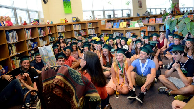 """Librarian Sandra Nagy reads """"Oh, the Places You'll Go,"""" by Dr. Seuss to Williamston High School seniors at the elementary school library after they walked the hall and gave high-fives to students  on one of their last days in the district before graduation. Nagy has been librarian to many of the students since they were in kindergarten."""