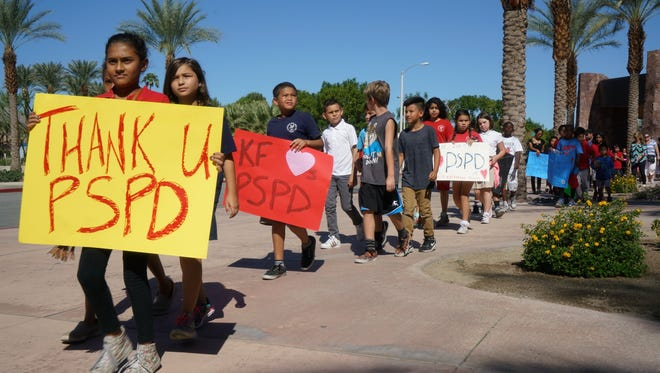 Fourth-graders from Katherine Finchy Elementary School walk outside the Palm Springs Convention Center, showing signs of support for the two fallen police officers, Gil Vega and Lesley Zerebny, before Tuesday's memorial service for the officers. The two were ambushed and gunned down during an Oct. 8 domestic disturbance call.