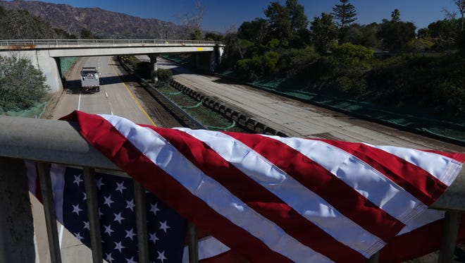 Winds blew a flag over the guardrail of the Olive Mill Road overpass on Highway 101 in Montecito Saturday. The freeway is expected to reopen for the Monday morning commute, Caltrans officials said. It has been closed since Jan. 9's deadly mudslides.