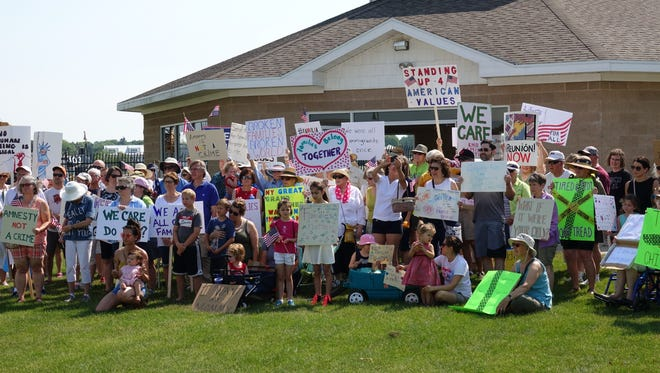 """Rally participants posed for a group photo with signs they made for the Sturgeon Bay """"Families Belong Together"""" march Saturday, June 30, 2018."""