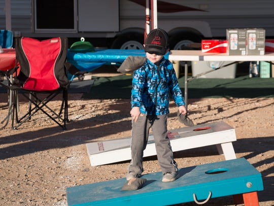 Lucas Harper tosses bean bags at his family's campsite