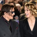 US actor Johnny Depp (L) jokes with fiancee US actress and model Amber Heard (R) as they arrive for the UK premiere of the film 'Mortdecai' in London on January 19, 2015.
