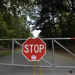 A gate blocks off a portion of the closed Smith Road in Greenville on Friday, August 21, 2015.