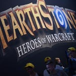 """Visitors pass a display for the """"HEARTHSTONE"""" game in August 2014 during the Gamescom fair in Cologne, Germany."""