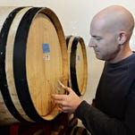 Jeff Albarella pours a beer sample from one of many barrels at Barrel House at Jessup Farm on Thursday, October 29, 2015. The brewery will open in November with a variety of barrel-aged beers.