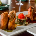 A platter of calamari fries with an Asian slaw, front, and a trio of duck lumpia, a poached slamon roll and seasame chicken wings are served up at Papa's restaurant in Barrigada on Wednesday, Nov. 4.