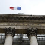A file photo from August shows a French flag on the pediment of the Palais Brongniart, the former French stock market. French stocks were resilient after attacks killed scores of people in Paris on Friday, reprising a trend where reactions to terror incidents have become increasingly short-lived.