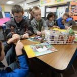 Western Wayne Elementary School Principal Renée Lakes, left, plays with Ian Bates and Caden Ripberger while visiting a second grade class Thursday, Feb. 4, 2016, as the school in Cambridge City participates in Global Play Day.