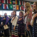 Students lead a group of new United States citizens in the Pledge of Allegiance during a naturalization ceremony at Dunn Elementary School  in Fort Collins Friday, March 4, 2016. 26 people from around the world were granted citizenship during the event.
