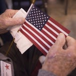 A veteran holds an American flag at the Island Grove Events Center in Greeley before departing to Denver International Airport for a Honor Flight Northern Colorado trip in September 2015.