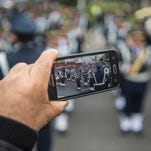 A man records a video of troops during a military parade to celebrate Peru´s Independence Day in Lima on July 29, 2016.