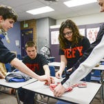 From left, John Francis, Guy Peters, Sabra Renner and Reilly Scheffing reach for stickers to hand out to friends during Windsor High School's Defy group meeting in February. Defy is a group that promotes not drinking or using drugs. Surveys about youth's drug use and sex lives are under new scrutiny from parents who call them invasive and inappropriate.