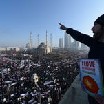 Chechen Muslims gather in downtown regional capital of Grozny to take part in a protest rally on Monday, Jan. 19, 2015. Protesters have gathered in the Russian region of Chechnya to rally against the French satirical magazine Charlie Hebdo, where 12 people were killed by gunmen this month. Chechen central Mosque is at background. (AP Photo/ Musa Sadulayev) ORG XMIT: MOSB106