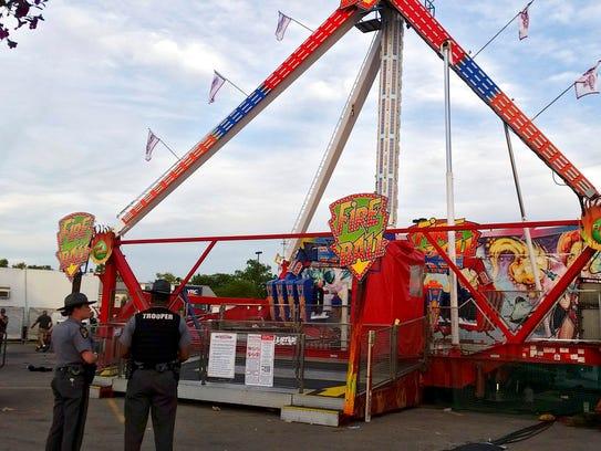 Authorities stand near the Fire Ball amusement ride