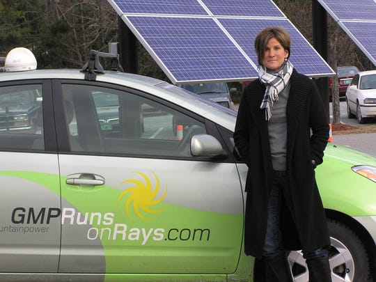 Green Mountain Power's Mary Powell stands near a plug-in hybrid car and solar panels at the utility's Colchester office. The panels produce enough electricity to power the plug-in hybrid vehicles.