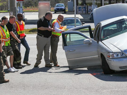 Scott Stoller, middle, Anderson County EMS & Special Operations Division Chief, looks over the shoulder of Anderson County Deputy Coroner Don McCown, right, into a Lincoln Continental at the scene of a wreck Friday afternoon at S.C. 24 and Whitehall Road. South Carolina Highway Patrol officers, Centerville volunteer firemen, and MedShore worked the accident in which a Mack truck from Powell's Trash Services collided with a beige Lincoln Continental shortly after noon. The truck driver was unharmed but the driver in the car was taken to AnMed Health by MedShore ambulance service.