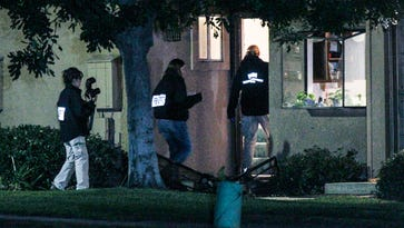 FBI agents search outside a home in connection to the shootings in San Bernardino, Thursday, Dec. 3, 2015, in Redlands, Calif..