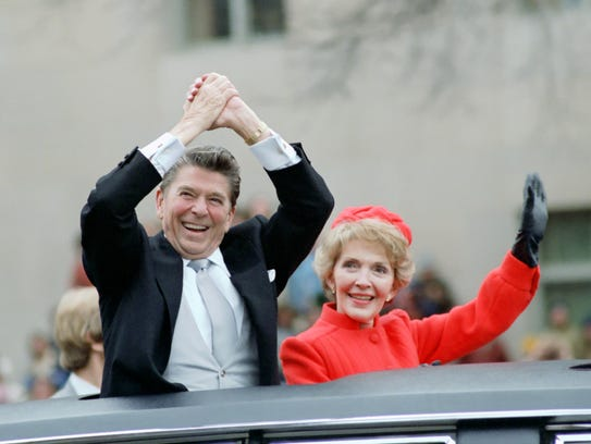 The Reagans wave from the limousine during the inaugural