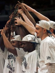 Members of the Michigan State basketball team hold