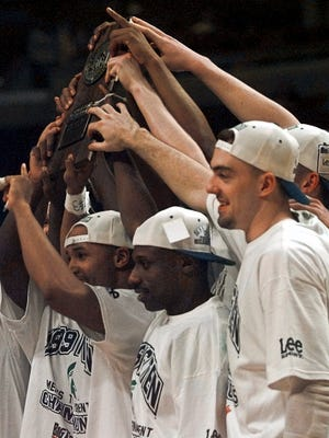 Members of the Michigan State basketball team hold up their Big Ten Championhip plaque after winning the tournament in Chicago, Sunday, March 7, 1999. Michigan State defeated Illinois 67-50 to clinch the Big Ten title.