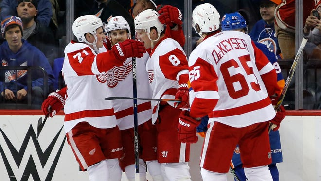 From left, Wings forwards Dylan Larkin and Henrik Zetterberg celebrate with Justin Abdelkader after his goal as defenseman Danny DeKeyser looks on in the second period of Monday night's 4-2 victory in New York.