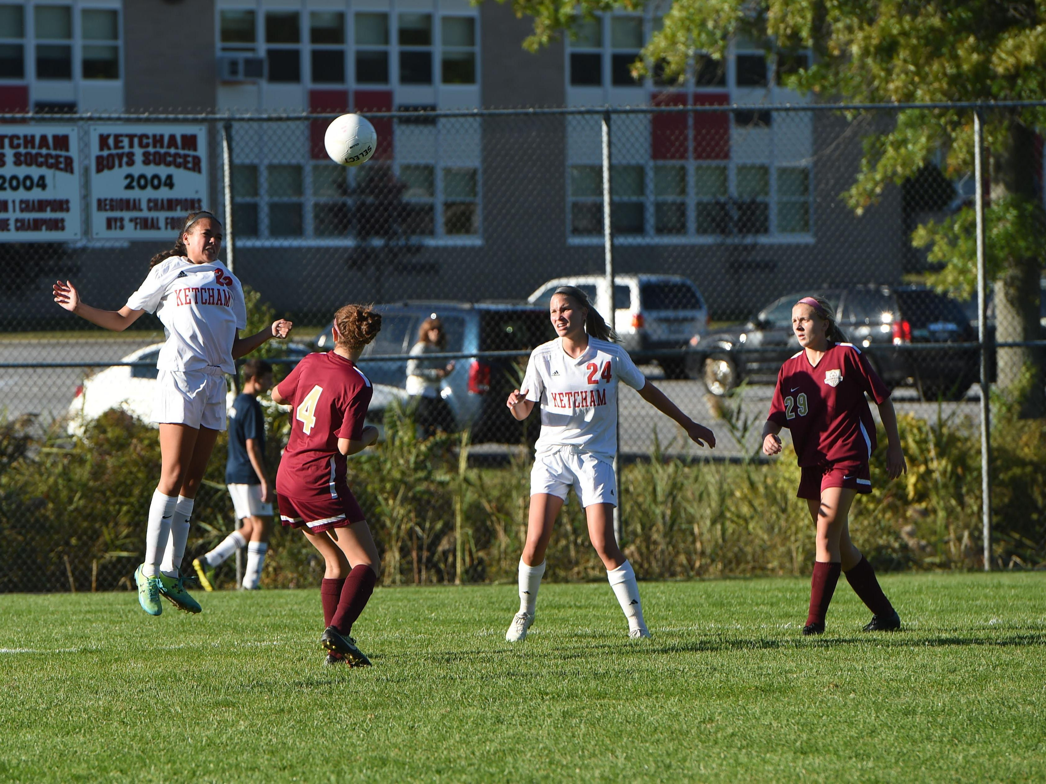 Ketcham's Jolinn Alonzo, left, heads the ball down field as teammate Emily Bender, center right, and Arlington's Michaela Fasalino, center left, and Molly Feighan, right, look on.